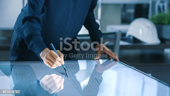 464482634istockphoto Talented Young Female Architectural Designer Draws Building Concept on a Graphics Tablet Display Vertical Touchscreen Table. Clean Minimalistic Office, Concrete Walls Covered by Blueprints. 921019762