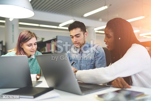 905130626 istock photo Talented young journalist working on creation article for online issue talking to each other sitting in office,male and female students doing homework task searching information for project via laptop 903762936