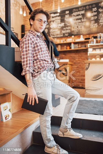 1174436608 istock photo Talented young man in casual shirt drawing sketch in notebook enjoying leisure time in coffee shop.Skilled student writing down homework in notepad sitting in coworking 1136774835