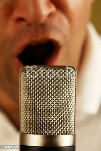 Man singing or talking laudly behind a professional microphone