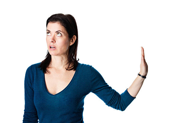 Talk to the hand Fed up mature woman in a blue top gestures to talk to her hand to her right while looking up in exasperation. rolling eyes stock pictures, royalty-free photos & images