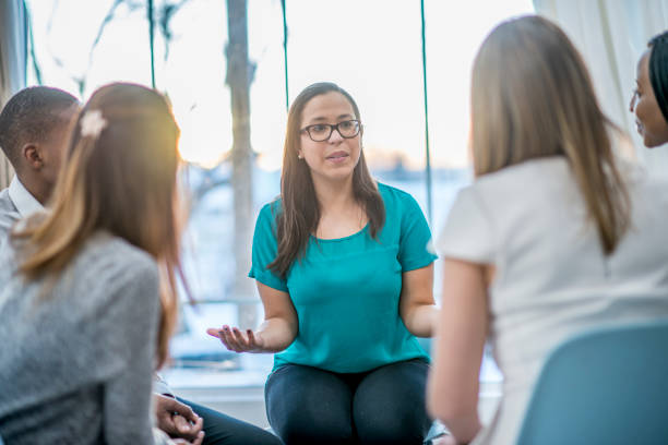 Talking About Problems A multi-ethnic group of adults are attending a mental health support group. A Caucasian woman is telling the rest of the group about her problems. group therapy stock pictures, royalty-free photos & images