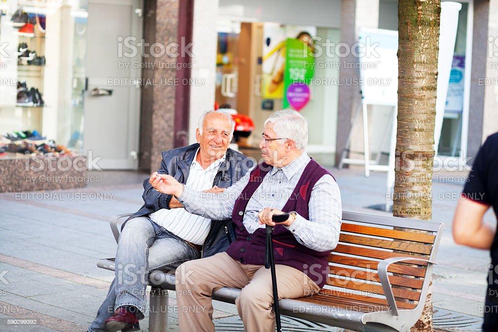 Talking and sitting on bench royaltyfri bildbanksbilder