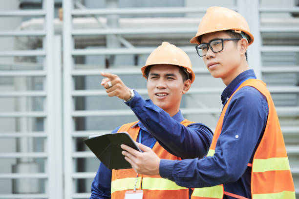 Talking engineers Young professional engineers discussing problem on production facility vietnamese ethnicity stock pictures, royalty-free photos & images