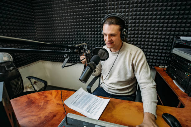 Talking male radio presenter read text on paper in radio station Talking male radio presenter read text on paper in radio station. radio dj stock pictures, royalty-free photos & images