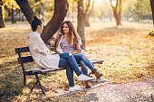 Two female friends talking on a bench in autumn park