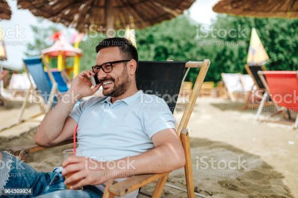 Foto de Falando Ao Telefone Na Praia Closeup e mais fotos de stock de Adulto
