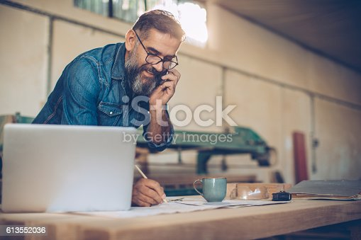 Carpenter in wood workshop using phone and working on project. Mature man in casual clothing. Space is full of working tools and wooden planks.
