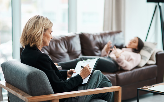 Shot of a mature psychologist writing notes during a therapeutic session with her patient