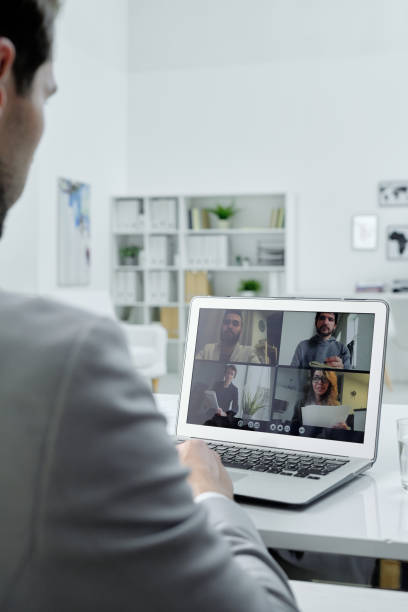 Talking to colleagues via video conferencing stock photo