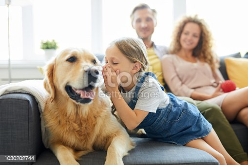 Little girl whispering something to her pet while relaxing on sofa on background of young couple
