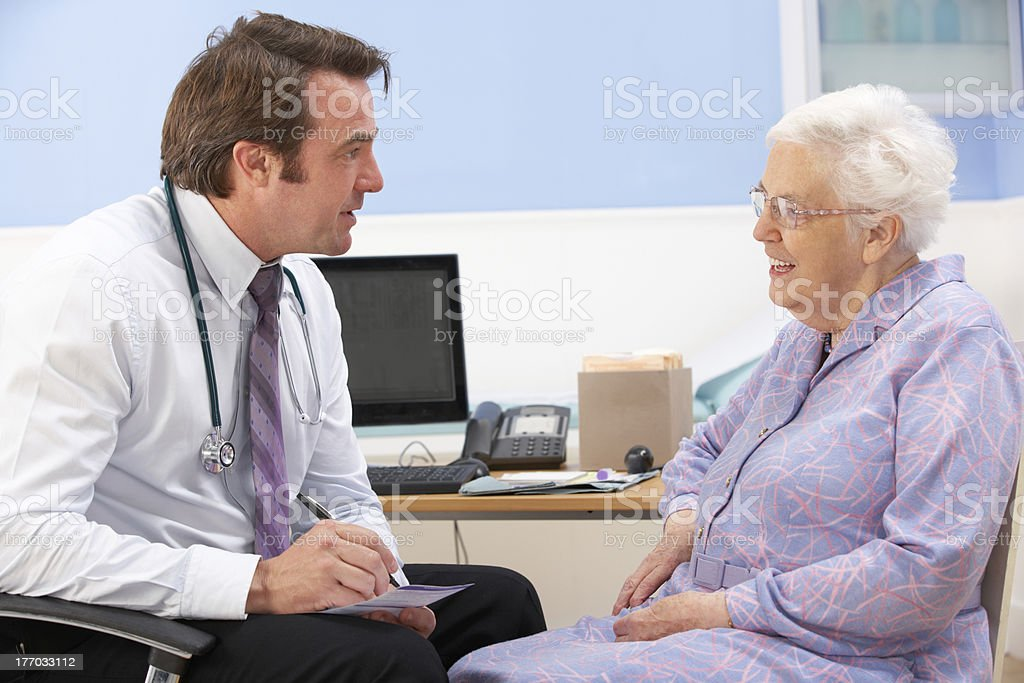 UK GP talking to senior woman patient royalty-free stock photo