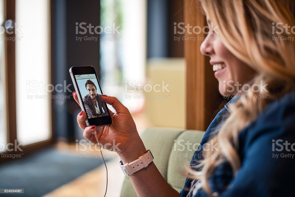 Talking with an old friends Woman is having a video call with an old friend on a mobile phone. Adult Stock Photo
