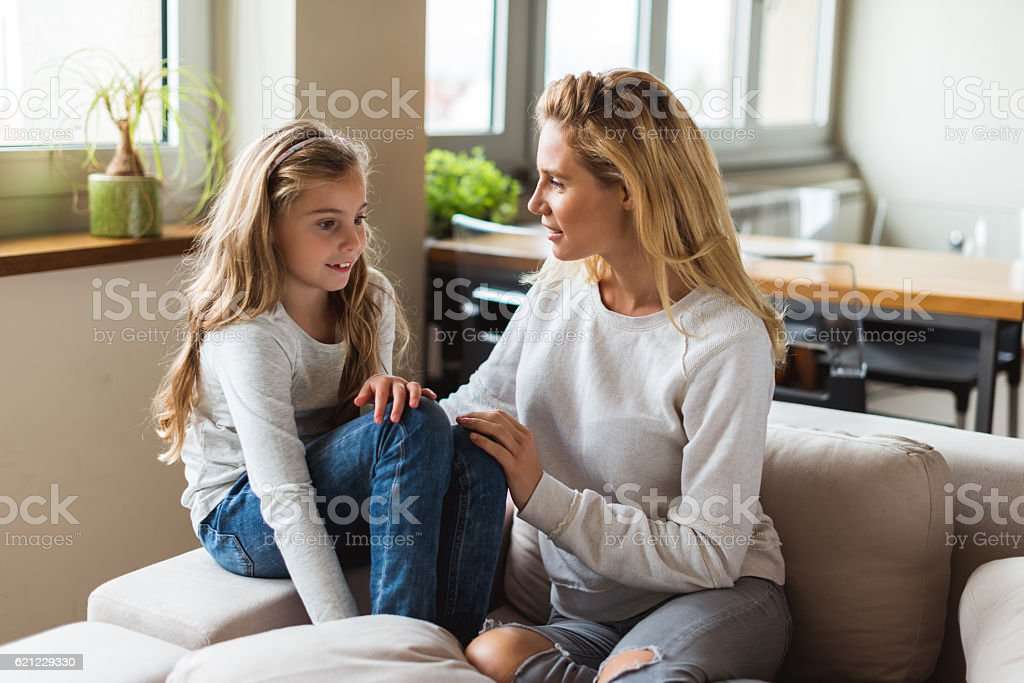 Talking with mom Mom and daughter sharing a love moment at home. Adult Stock Photo