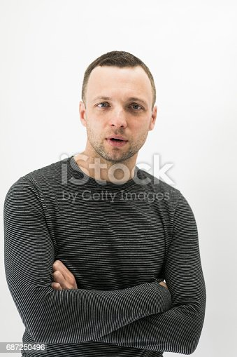 Close-up vertical studio portrait of young adult European man over white wall