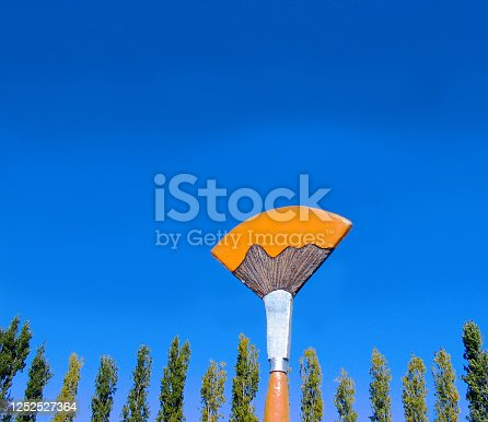 A temporary art festival sign in the form of a huge paint brush against a blue sky.  A great image and background to represent artists, especially painters.