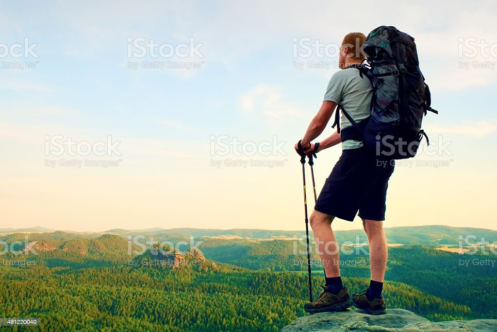 Tall backpacker with poles in hand. Sunny summer evening stock photo