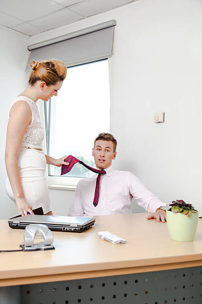 tall blonde secretary flirts with young boss in office stock photo