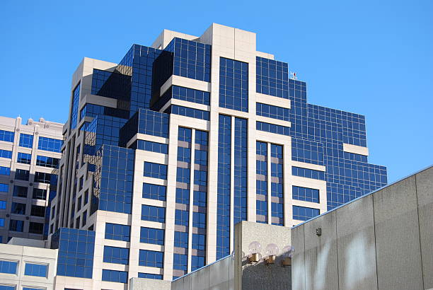 Tall blue and white office building against a clear blue sky stock photo