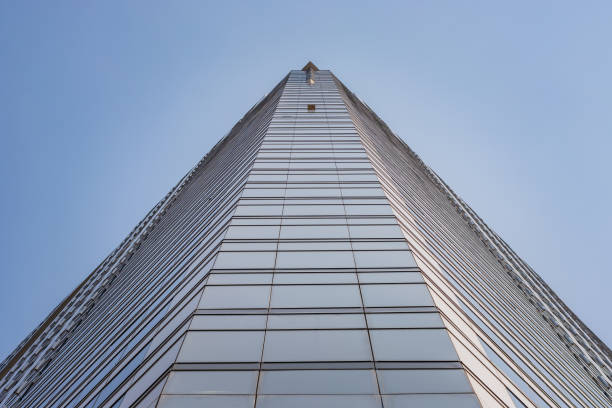 Tall building with blue glass windows in Bangkok, Thailand, view and perspective from the ground, blue sky above – zdjęcie