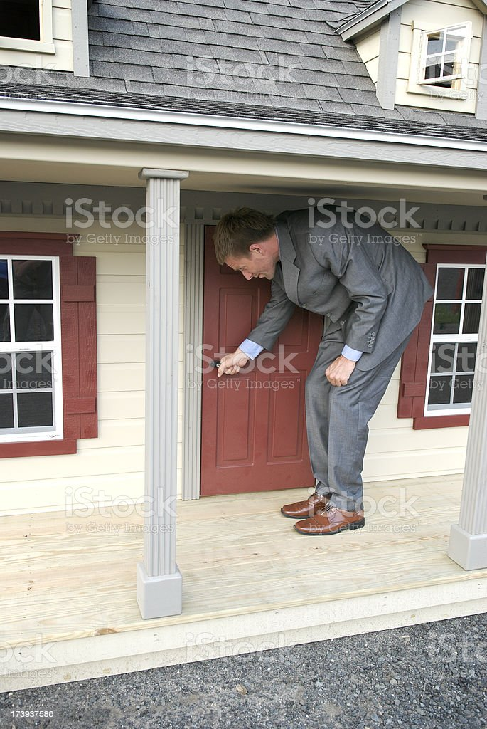 Tall Businessman Entering Front Door of Small House stock photo