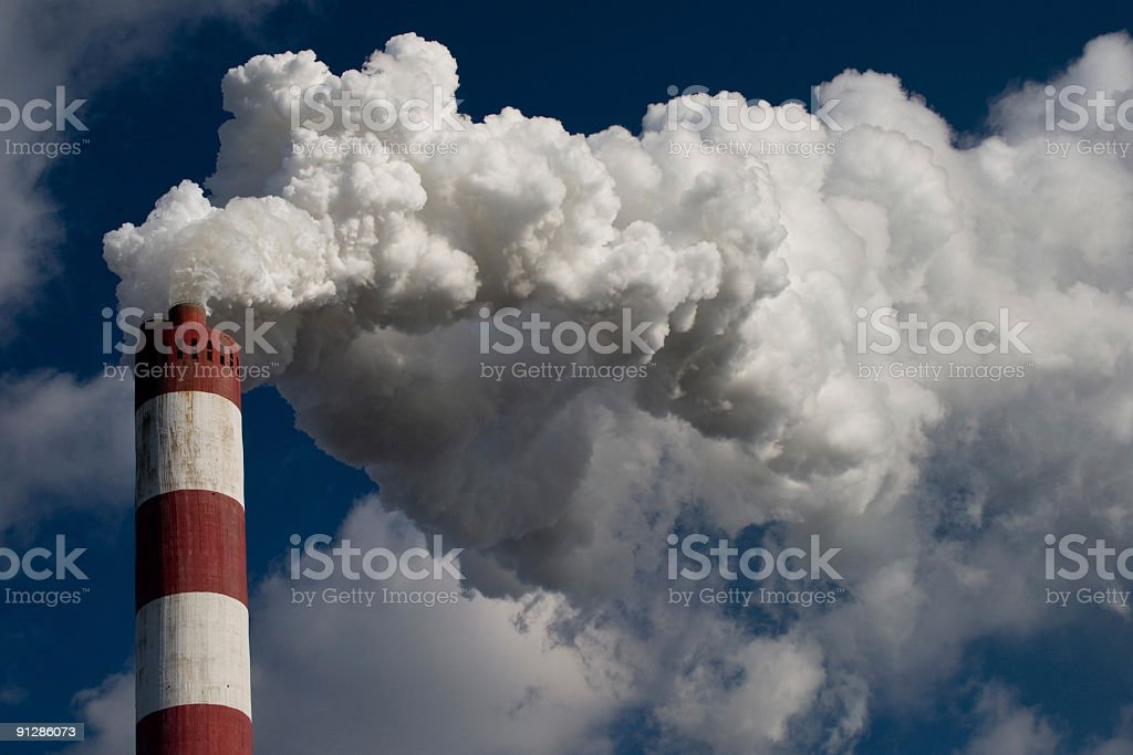 A tall chimney blowing white thick smoke to the sky stock photo