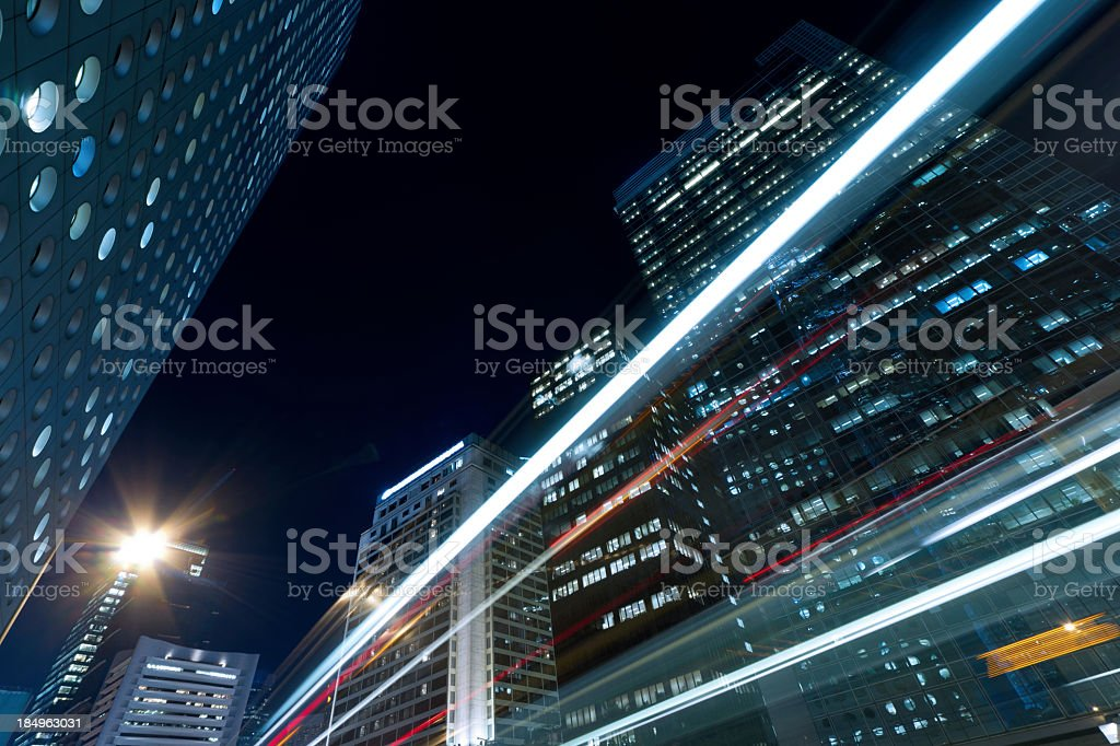 Tall city buildings at night with blur traffic lights royalty-free stock photo