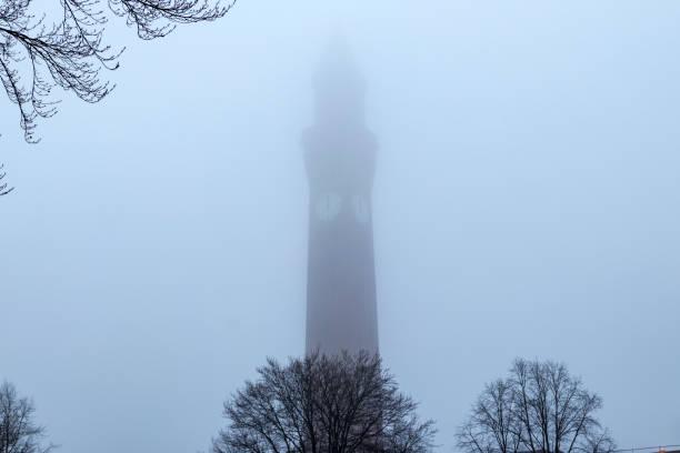 Tall clock tower vanishing into the mist stock photo