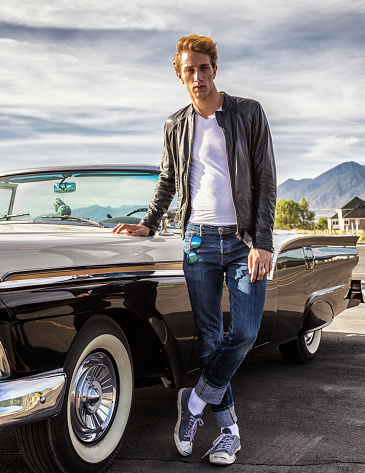 Tall Cool Fifties Greaser Guy Standing With Convertible Classic Car
