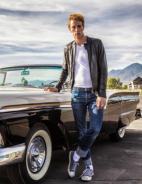 große coole fifties greaser mann stehend mit cabrio oldtimer - lange jacken stock-fotos und bilder