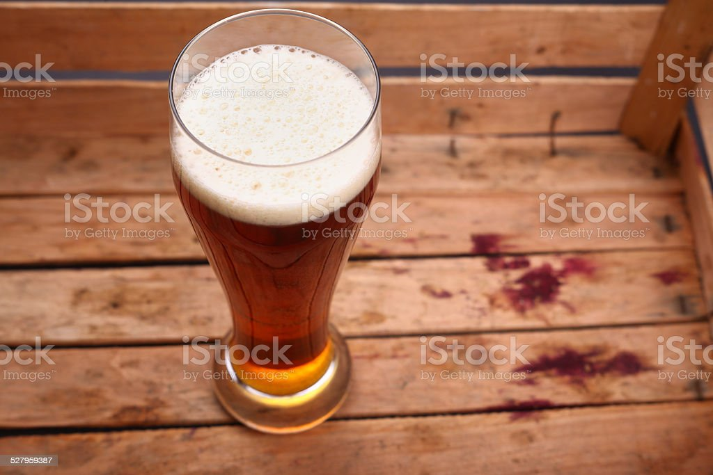 Tall glass of beer in a crate stock photo