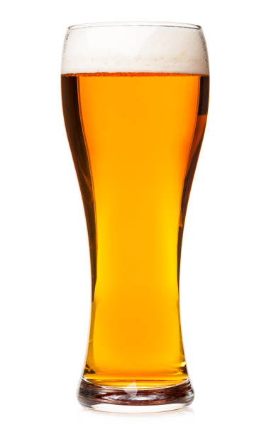 Tall glass of pilsner beer with head isolated Full pilsner glass of pale lager beer with a head of foam isolated on white background pilsner stock pictures, royalty-free photos & images