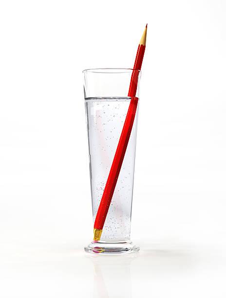 tall glass of water, with a red pencil inside. - lichtbreking stockfoto's en -beelden