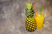 Tall glass of yellow fruit drink with ice and ripe pineapple beside on gray background. Close-up.