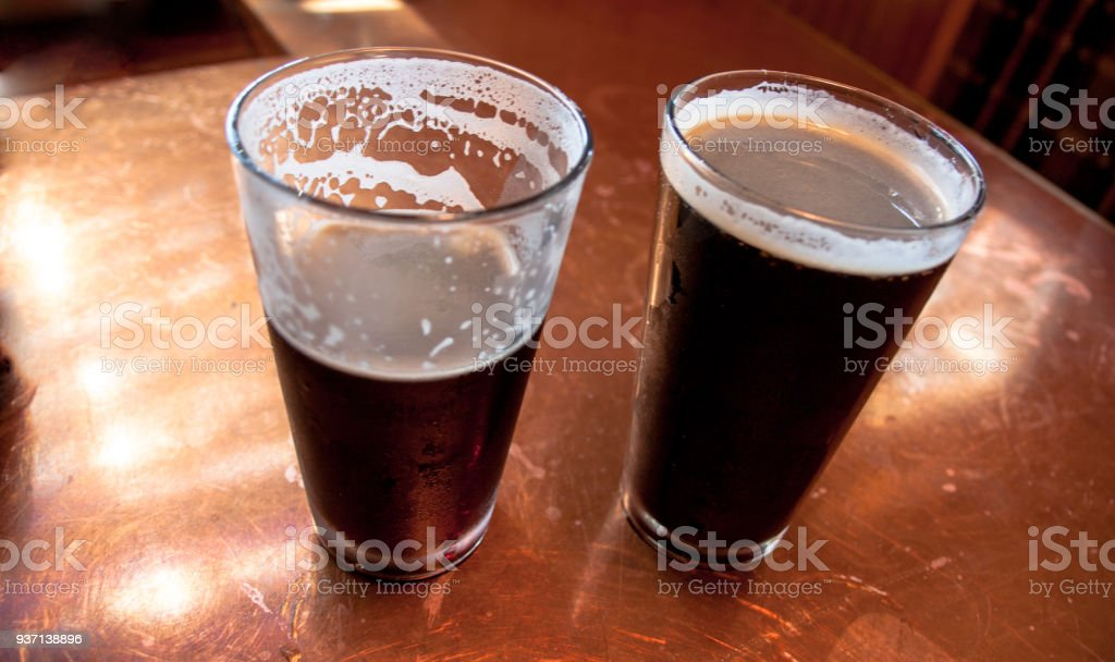 2 tall glasses of dark beer on a copper top table with 1 half empty 2 tall glasses of dark beer on a copper top table with 1 half empty royalty watchthetrailerfo
