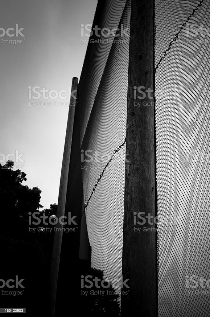 Tall golf fence in black and white stock photo