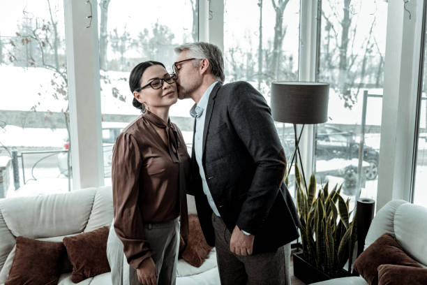 tall grey-haired handsome man in a blue shirt kissing a woman on a cheek - brunette woman eyeglasses kiss man foto e immagini stock