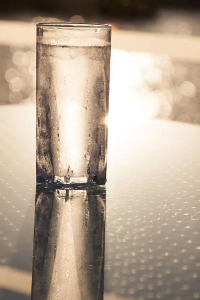 cam masaya yansıyan su damlaları ile uzun buzlu soğuk bardak su - salud stok fotoğraflar ve resimler