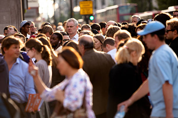 Tall man in a crowded intersection stock photo