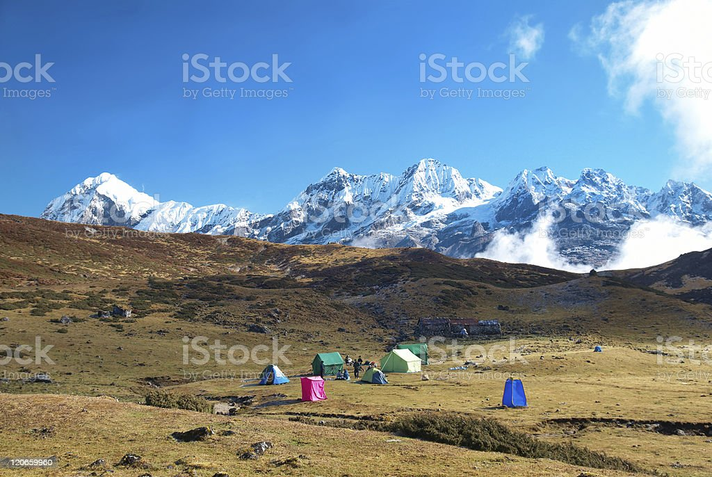 Tall mountains covered with snow and a campsite stock photo