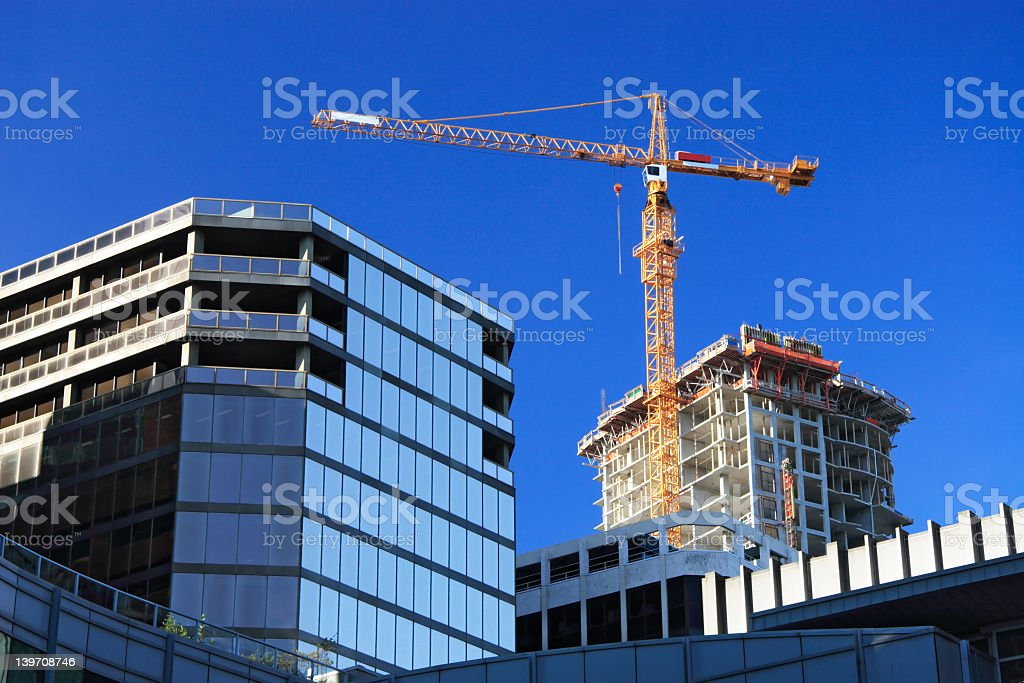 Tall orange crane towering over glass building royalty-free stock photo