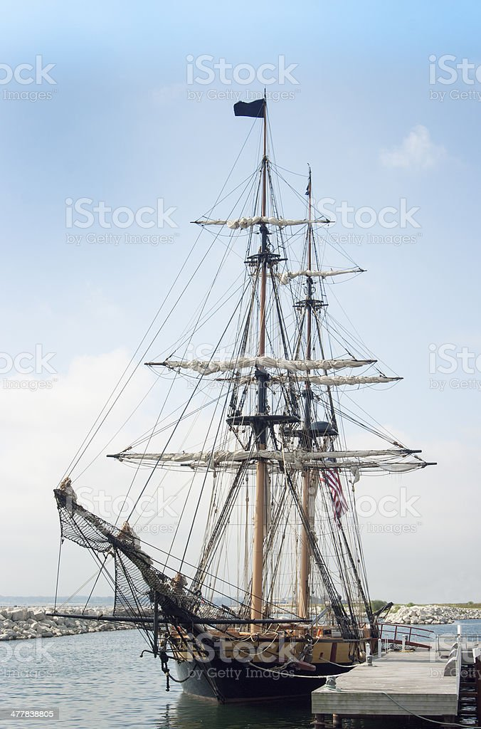 Tall Sailing Ship Harbored at Dock Pier Under Blue Sky royalty-free stock photo