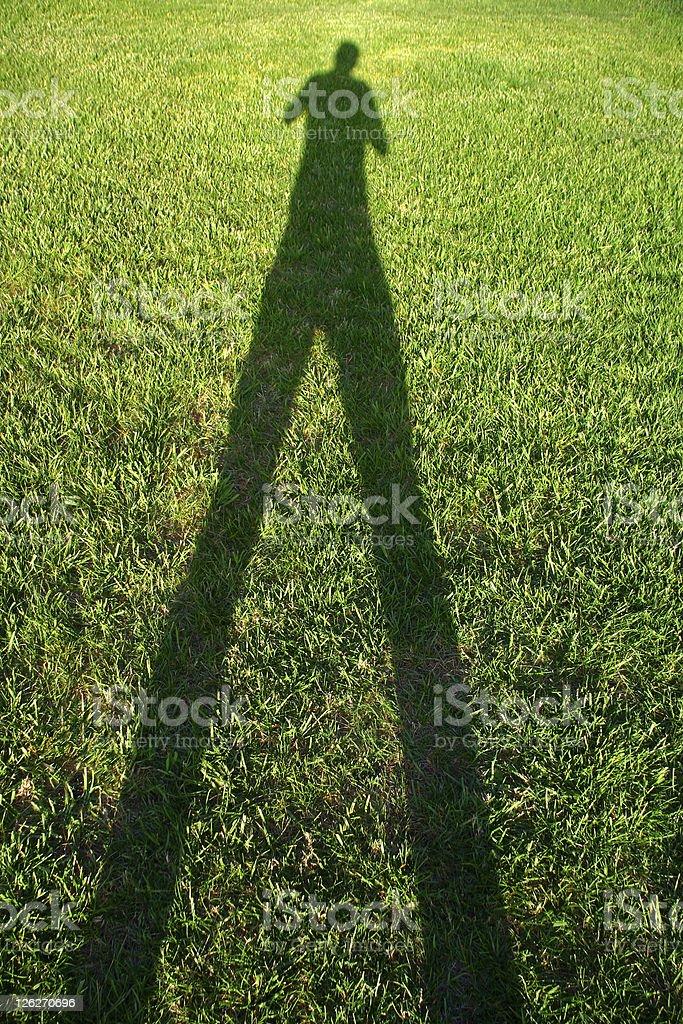 Tall Shadow Man - shadow on green grass stock photo