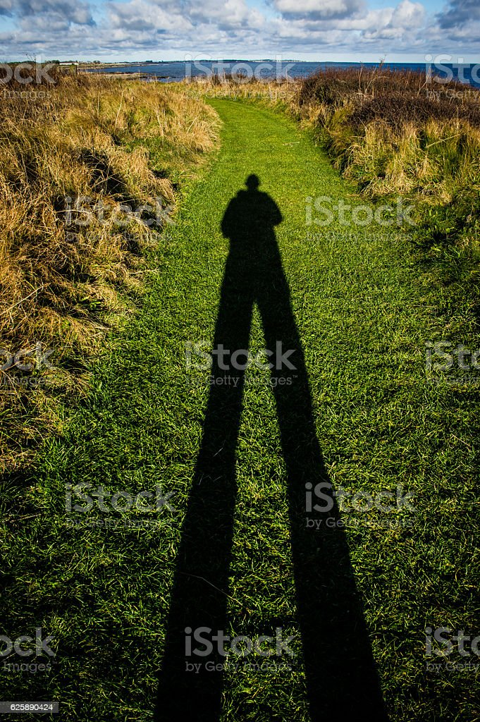 Tall shadow of man on grass path stock photo