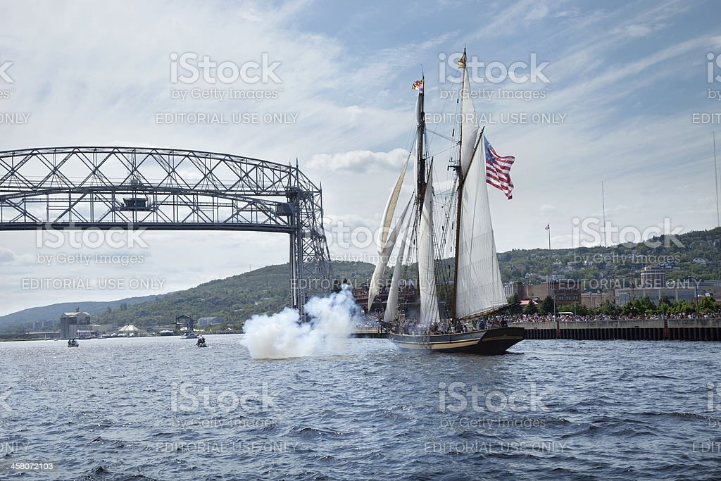 Tall ship enters Duluth harbor with cannons firing stock photo