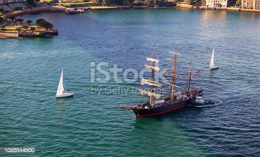 As seen from the Sydney Harbour Bridge, sailing ships, including the three masted ship James Craig, sail across Sydney Harbour on a beautiful Spring day.