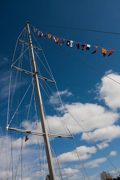 Tall Ship mast and flags with blue sky background stock photo