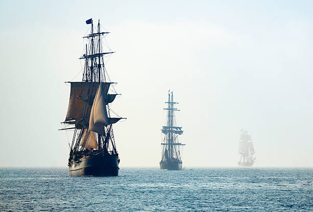 tall ships in the last mists of morning fog - pirates stock photos and pictures