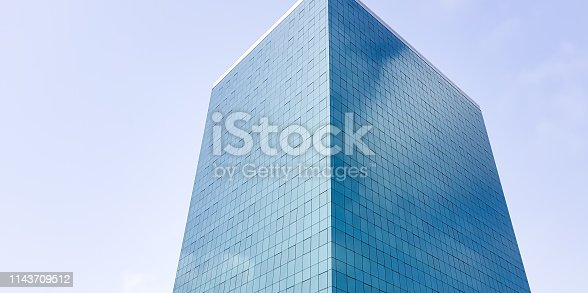 1157587322 istock photo Tall skyscraper with glass facade, reflecting clouds in the sky. Business corporation office building. 1143709512