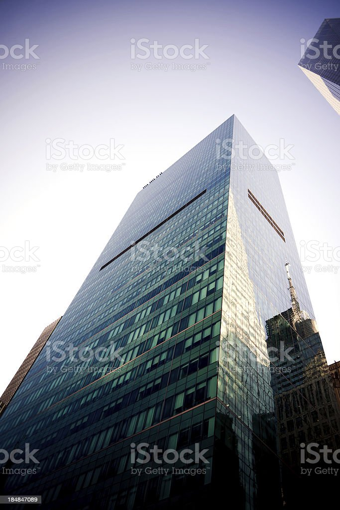 A tall skyscraper with glass reflecting in New York City royalty-free stock photo